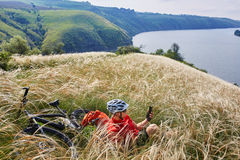 Young cyclist resting on the meadow on reverside in mountains with mountain bicycle against beautiful sky. Stock Images