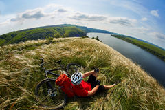 Young cyclist resting on the meadow on reverside in mountains with mountain bicycle against beautiful sky. Royalty Free Stock Image