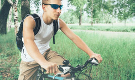 Young cyclist riding on bicycle in summer park Stock Image