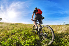 Young cyclist riding mountain bicyclist against beautiful sunset in the countryside. Sportsman dressed in the black sportwear and sporty shoes, with helmet and Royalty Free Stock Photos