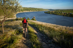 Young cyclist riding mountain bike uphill along a country road above river. Royalty Free Stock Image