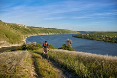 Young cyclist riding mountain bike uphill along a country road above river. Stock Photography