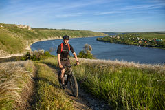 Young cyclist riding mountain bike uphill along a country road above river. Stock Photos