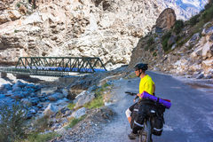 Young cyclist riding in mountain Himalayas. Man bicyclist in yellow t-short standing on mountain road Royalty Free Stock Images