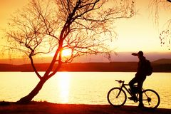 Young cyclist silhouette on blue sky and sunset background on beach. End of season at lake. Stock Photo