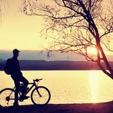 Young cyclist silhouette on blue sky and sunset background on beach. End of season at lake. Royalty Free Stock Image
