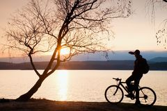Young cyclist silhouette on blue sky and sunset background on beach. End of season at lake. Stock Photography