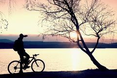 Young cyclist silhouette on blue sky and sunset background on beach. End of season at lake. Stock Images