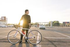 Young cyclist stands in a cap and sportswear stands with a white highway bike royalty free stock image