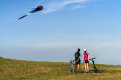 Young cyclists couple admire large flying multi colored kites at East Coast Park Stock Photo