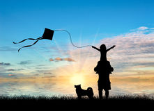 Young dad with child and dog playing with kite near sea Royalty Free Stock Photography