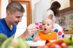 Young dad feeding baby and mom cooking at kitchen. Young dad feeding his baby and mom cooking at kitchen Royalty Free Stock Image
