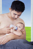 Young dad feeding his baby near the window Royalty Free Stock Photo