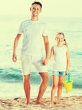 Young dad with girl standing on beach with toys Royalty Free Stock Photo