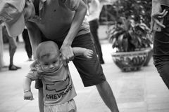 A young dad helps his kid walking. Black and white Royalty Free Stock Images