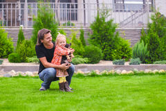 Young dad and his little daughter with her puppy on background their home Royalty Free Stock Image