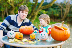 Young dad and his little son making jack-o-lantern for halloween Stock Photos