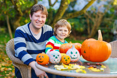 Young dad and his little son making jack-o-lantern for halloween Stock Photo