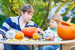 Young dad and his little son making jack-o-lantern for halloween. Little kid boy and his father making traditional jack-o-lantern for halloween in autumn garden Royalty Free Stock Photography