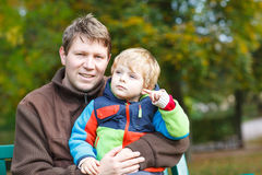 Young dad and his little toddler child in colorful clothes sitti Royalty Free Stock Photos