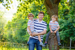 Young dad and his two little sons outdoors summer Stock Photos