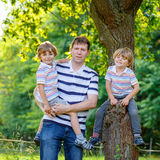 Young dad and his two little sons outdoors summer Royalty Free Stock Photos