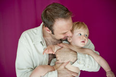 Young dad holding blonde baby boy Stock Images