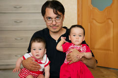 Young dad hugging his twin girls Royalty Free Stock Photo