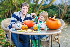 Young dad and kid son making jack-o-lantern for halloween in aut. Young dad and his little kid son making jack-o-lantern for halloween in autumn garden, outdoors Royalty Free Stock Images