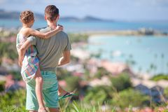 Young father and little girl enjoying beautiful views of exotic island. Young dad and kid with view of tropical white beach in exotic island in the Caribbean Sea royalty free stock images