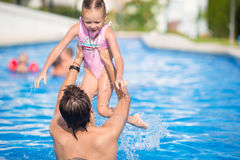 Young dad and little daughter playing in swimming pool enjoying summer vacation Royalty Free Stock Photography