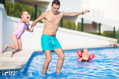 Young dad and little daughter playing in swimming pool enjoying summer vacation Stock Photo