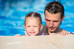 Young dad and little daughter playing in swimming pool enjoying summer vacation Stock Photos