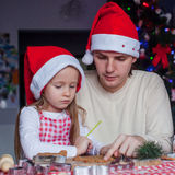 Young dad with little daughter in Santa hat bake. Christmas gingerbread cookies. This image has attached release royalty free stock image