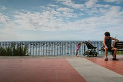 Dad with toddler daughter moving her stroller on a promenade at the sea in summer. Royalty Free Stock Photo