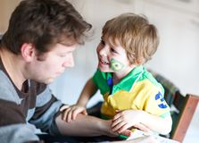 Young dad painting flag on face of little son for football or soccer game. Happy excited preschool kid boy fan and father preparing for game of favorite team stock image