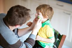 Young dad painting flag on face of little son for football or soccer game. Happy excited preschool kid boy fan and father preparing for game of favorite team stock photo