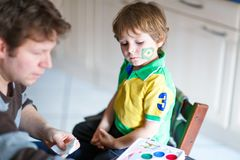 Young dad painting flag on face of little son for football or soccer game. Happy excited preschool kid boy fan and father preparing for game of favorite team royalty free stock images
