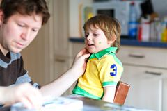 Young dad painting flag on face of little son for football or soccer game. Happy excited preschool kid boy fan and father preparing for game of favorite team royalty free stock image