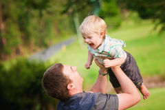 A young Dad playing with his little son outdoors. A cute little blond haired, blue eyed boy plays with his Dad in an outdoor field Royalty Free Stock Photo