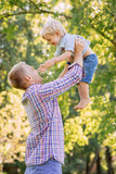 Young dad playing with his son in the park by throwing him up.  Stock Photos