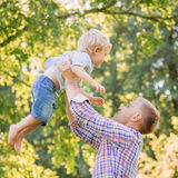 Young dad playing with his son in the park by throwing him up.  Royalty Free Stock Photo