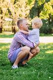 Young dad playing with his son in the park by throwing him up.  Royalty Free Stock Photography