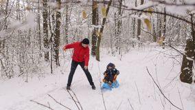 Young dad pushing son on a sled in winter alley. stock video footage
