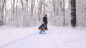 Young dad pushing son on a sled in winter alley. stock footage