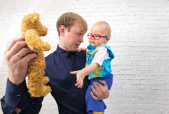 Young dad shows teddy bear to his one year old son on brick back. Young father shows teddy bear to his one year old son on brick white background Royalty Free Stock Images