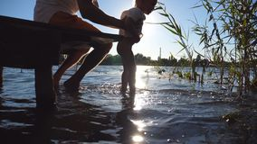 Young dad sitting on the edge of a wooden jetty at lake and holding his son in hands. Little child swinging feet in the. Water on a sunny day. Family spending stock footage