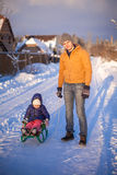 Young dad sledding his little daughter on a sunny Stock Photography