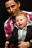 Young dad with son. Happy young dad or father with baby son, black studio background Royalty Free Stock Images