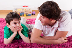 Young dad and son. A young handsome dad lying on the floor with his son Stock Photo